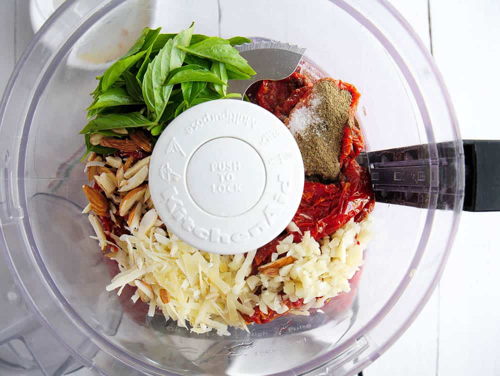 Ingredients for sun-dried tomato pesto in a food processor.