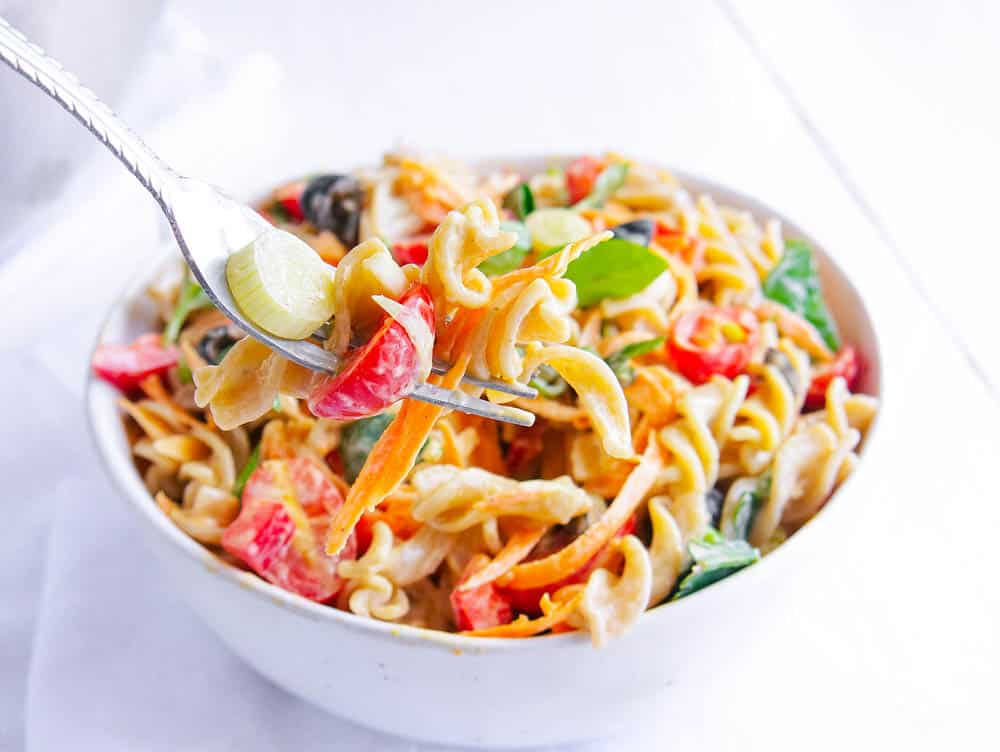 Protein Packed Pasta Salad with Olives and Herbs in a white bowl being eaten with a fork
