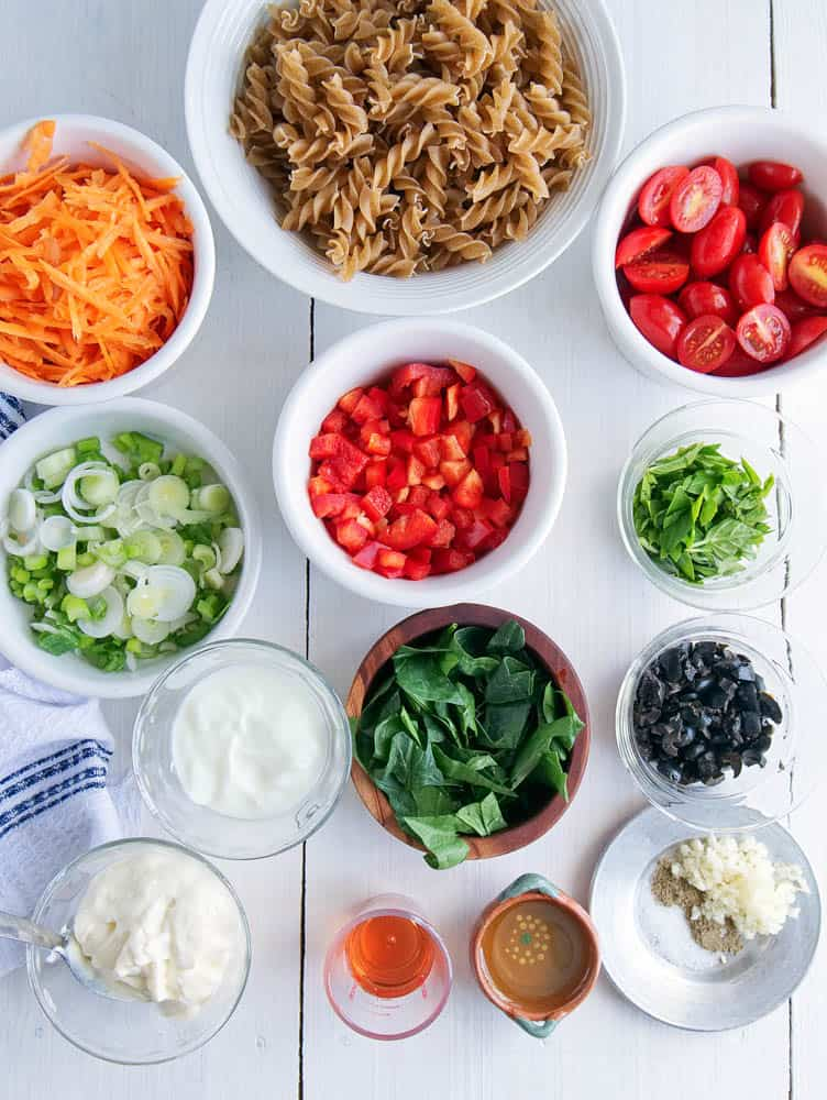 Ingredients for Protein Packed Pasta Salad with Olives and Herbs on a wooden work surface