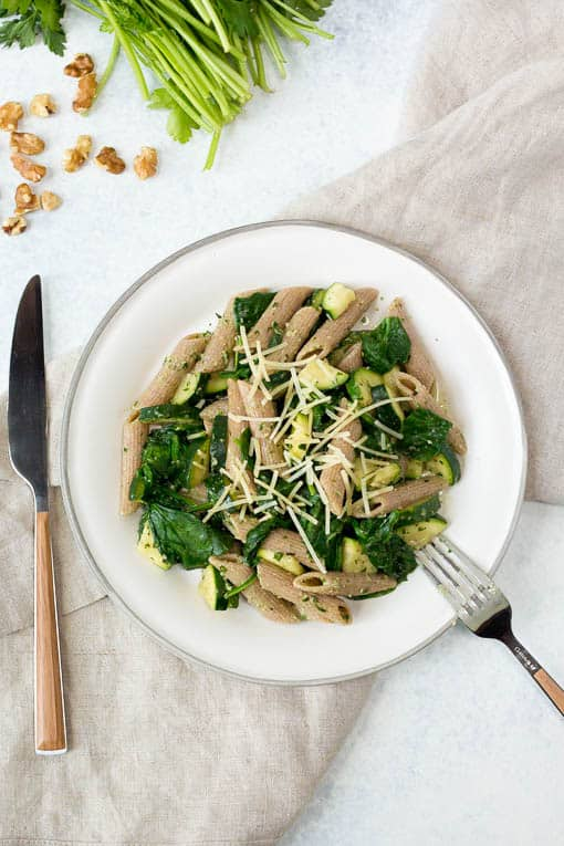 pesto without pine nuts served over whole wheat pasta on a white plate with a fork and knife