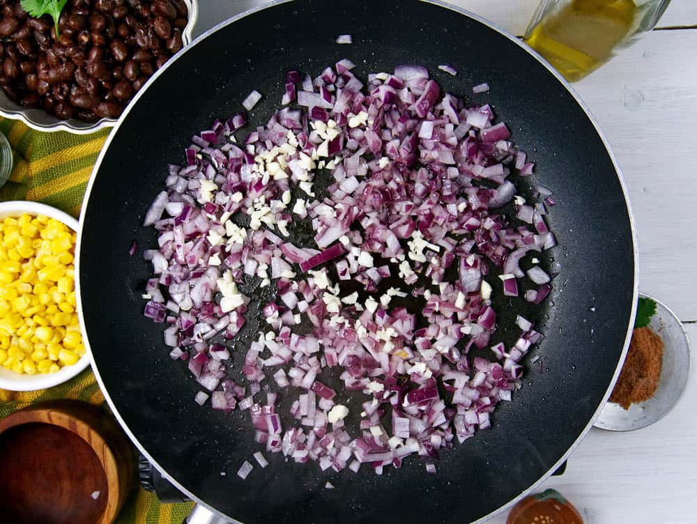 Red onion and garlic being cooked in a frying pan.