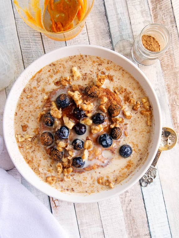 Top shot of Cinnamon and Spice Oatmeal with berries and pumpkin in a white bowl