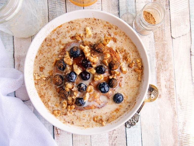 A bowl of Cinnamon and Spice Oatmeal with berries and pumpkin