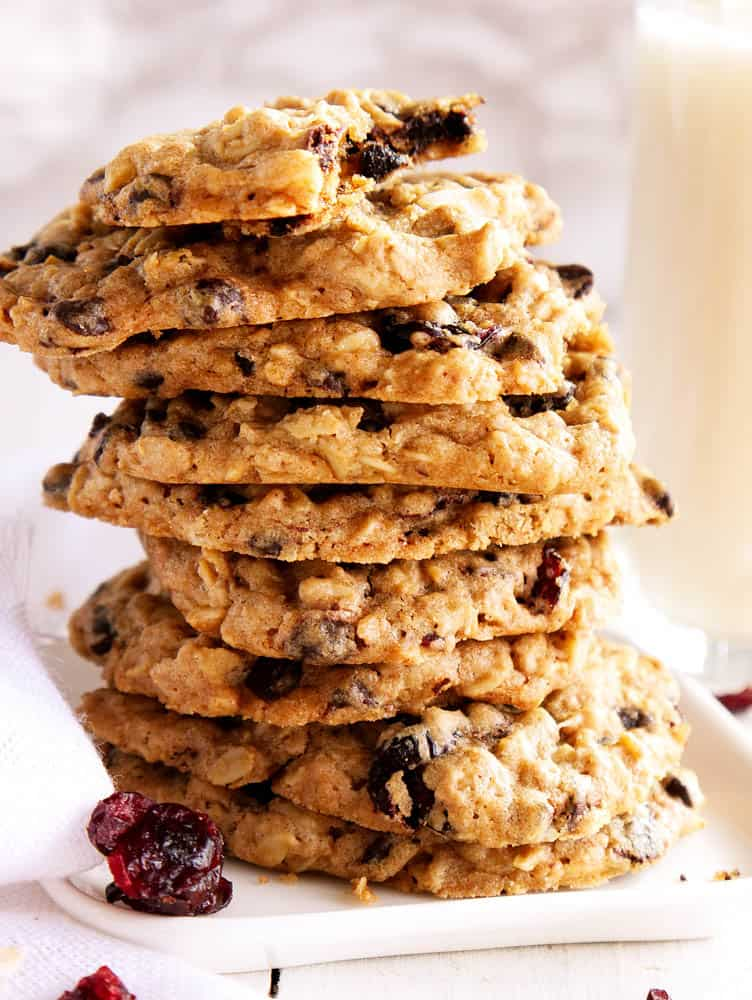 A stack of vegan oatmeal chocolate chip cookies with a bite taken out of the top cookie.