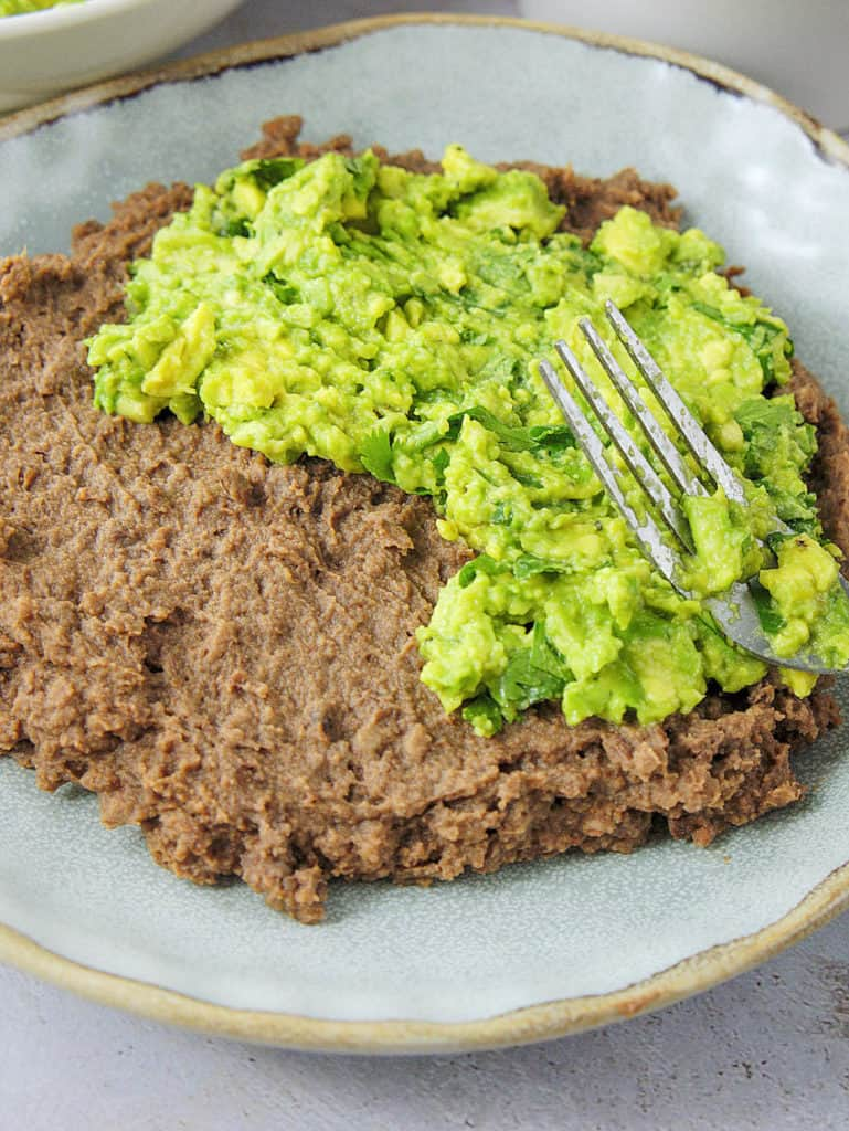 mashed avocado mixture spread on top of refried black beans