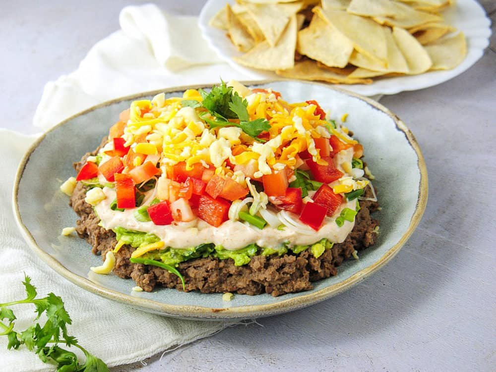 healthy 7 layer taco dip made with beans, avocado, greek yogurt, veggies and cheese, pictured on a blue plate with chips in the background.