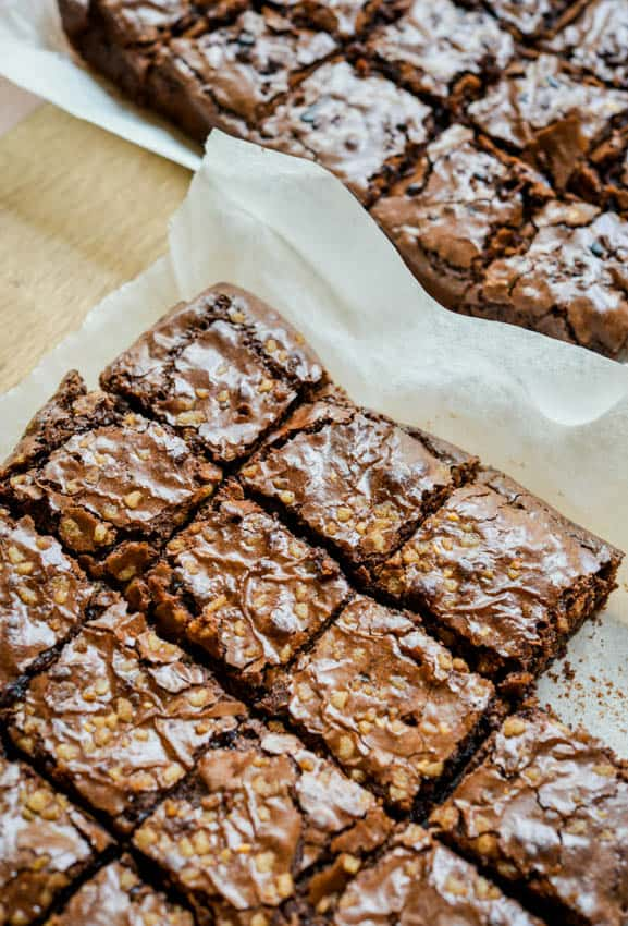 chocolate fudge brownies with walnuts cut into squares, placed on parchment paper