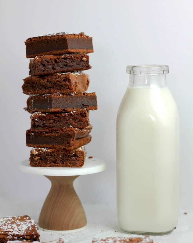 chocolate fudge brownies with walnuts, stacked on pedestal with glass of milk on the side