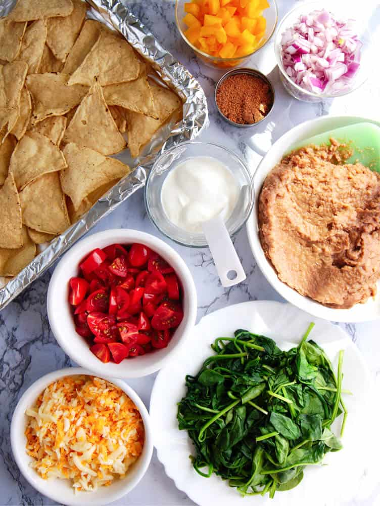 ingredients for late night nachos: chips, peppers, onions, beans, taco seasoning, tomatoes, greek yogurt and spinach