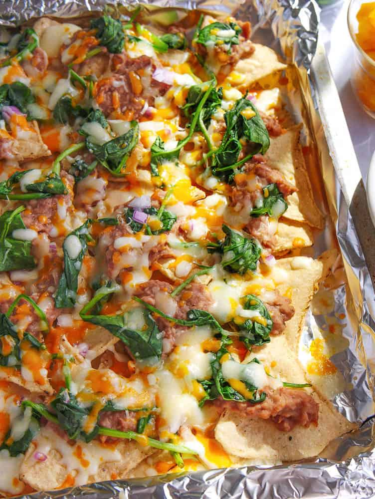 guilt free late night vegetarian nachos fresh out of the oven with onions, peppers, beans, cheese and spinach as toppings