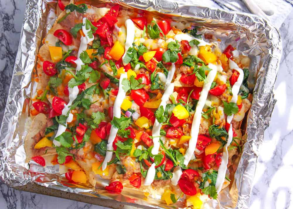 healthy guilt free late night nachos fresh out of the oven with tomatoes and greek yogurt added
