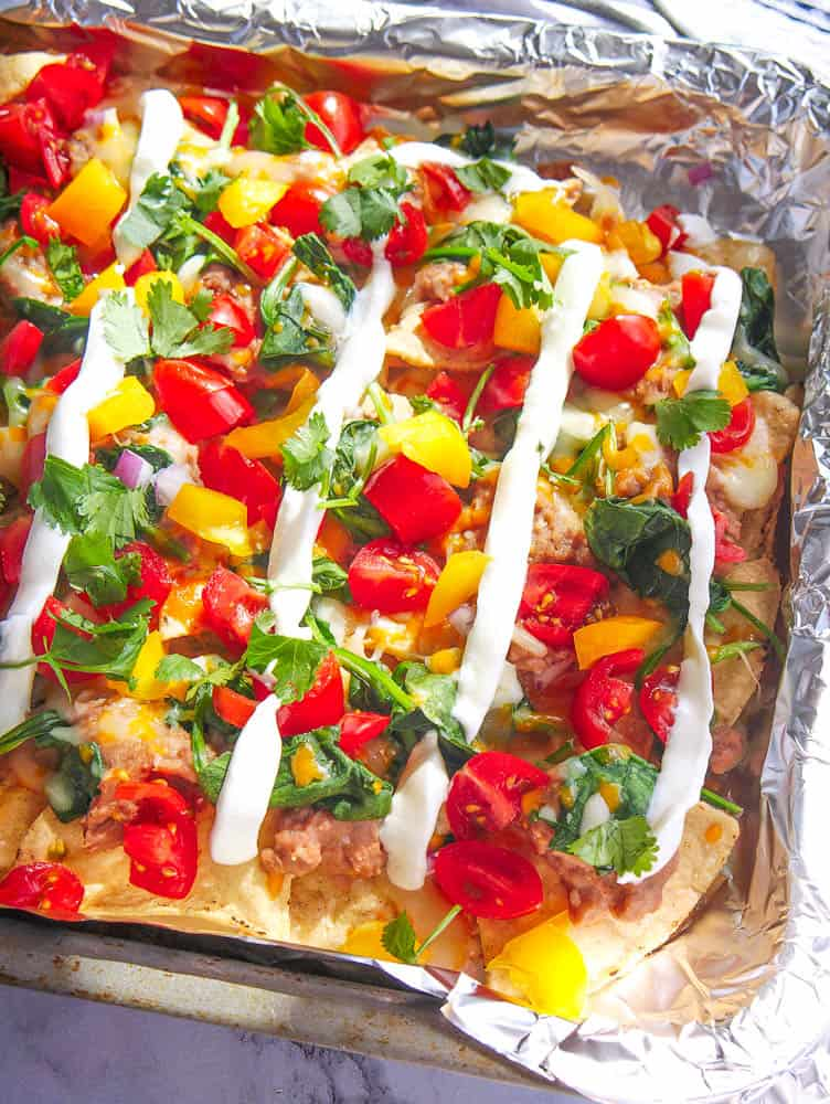 guilt free late night nachos topped with tomatoes, peppers, onions, cheese, beans and spinach on a baking sheet