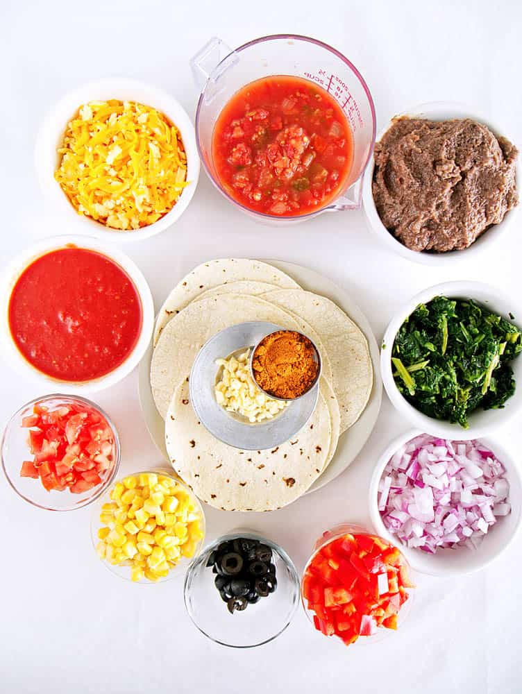 ingredients for vegetarian enchilada lasagna: tortillas, spices, corn, salsa, spinach, onions, tomatoes, refried black beans, olives and cheese