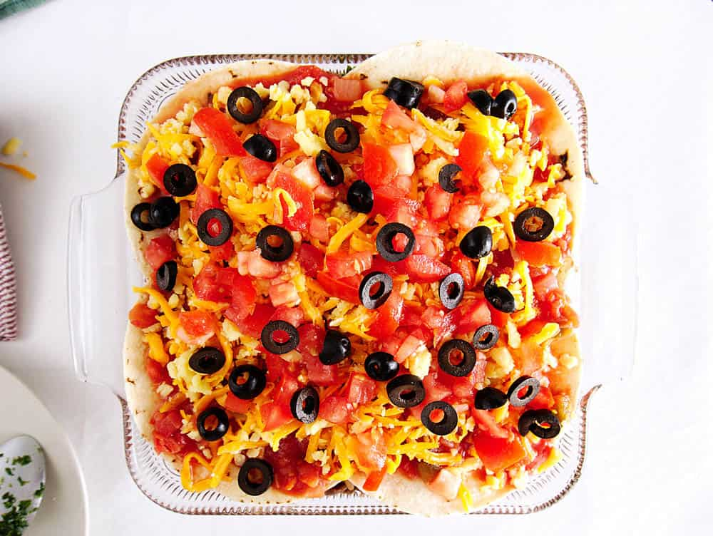 enchilada lasagna topped with cheese, salsa and olives