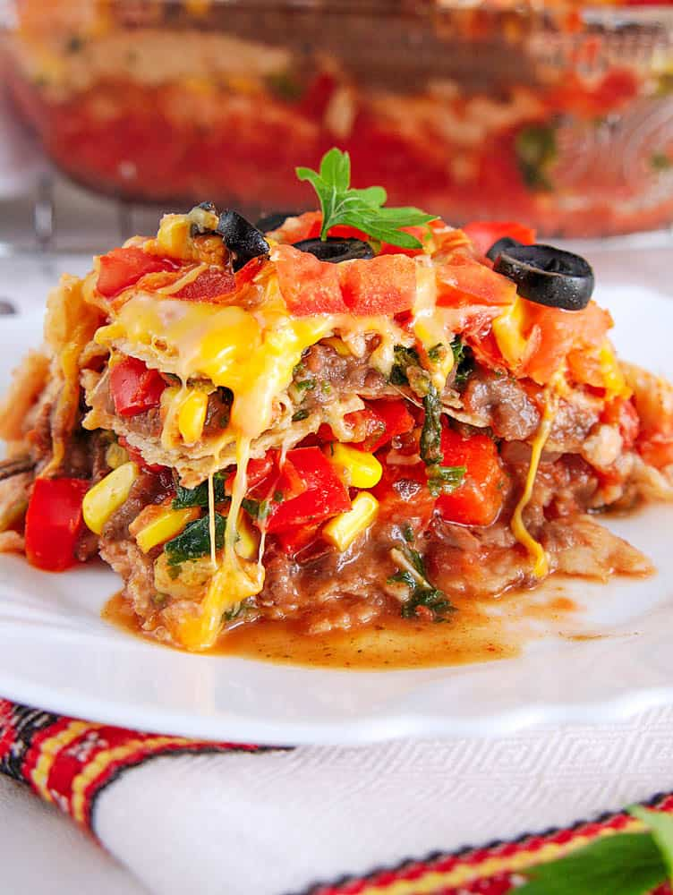vegetarian taco lasagna recipe, a piece cut and pictured on a white plate