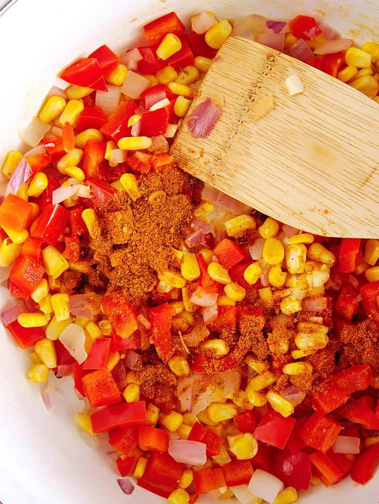 taco seasoning added to veggies in a pan