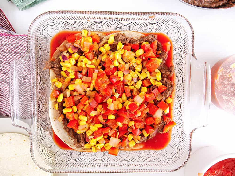 tortillas topped with refried beans, veggies and salsa