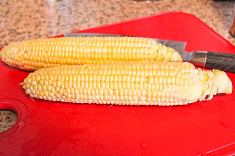 Two ears of corn on a red chopping board
