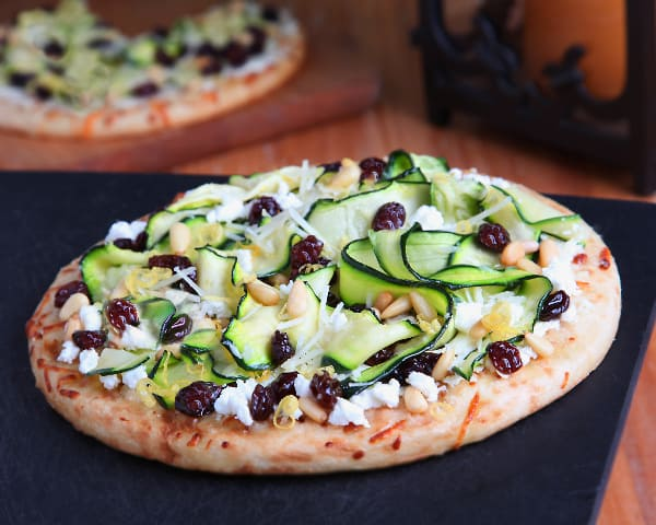 goat cheese flatbread with zucchini and raisins on a black cutting board
