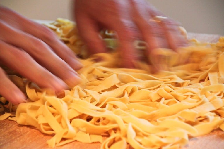 Homemade Tagliatelle being moved with hands