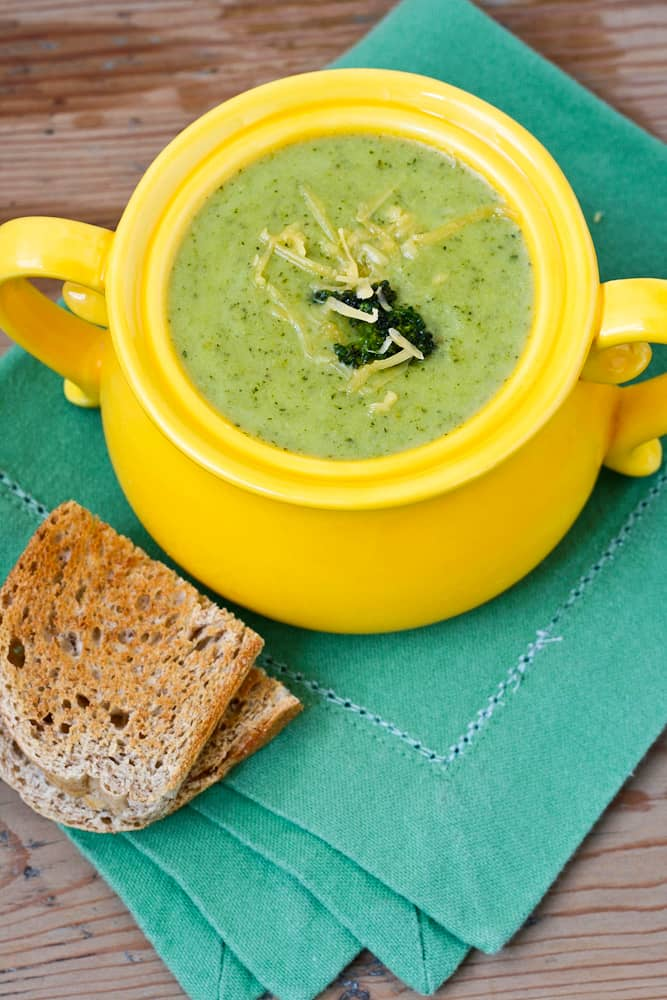 Healthy Cheddar Broccoli Soup in a yellow bowl with a green napkin against a wood background, top view
