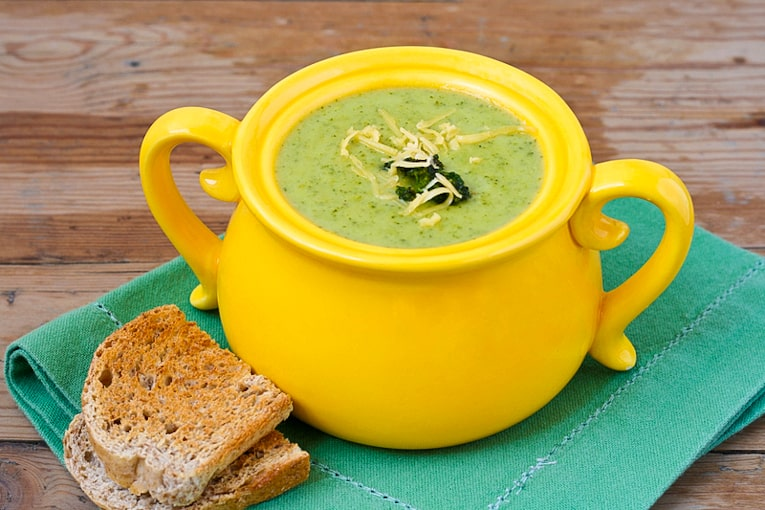 Healthy Cheddar Broccoli Soup in a yellow bowl with a green napkin against a wood background and toast on the side