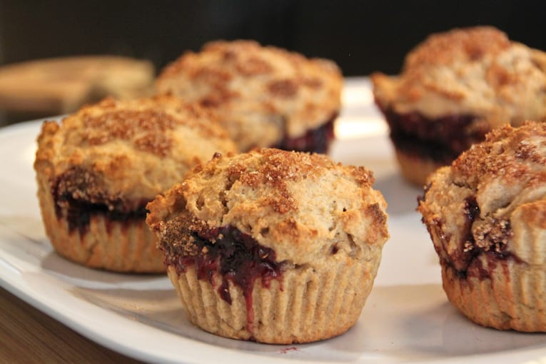 cinnamon sugar muffins filled with raspberry jelly on a white plate