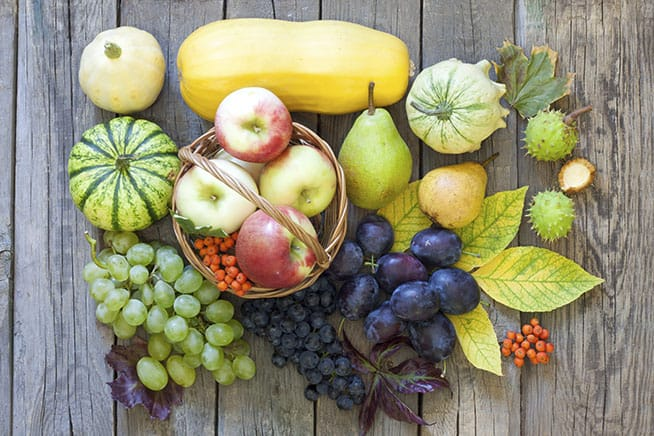 fruit on wood table, apples in basket, grapes, and squash