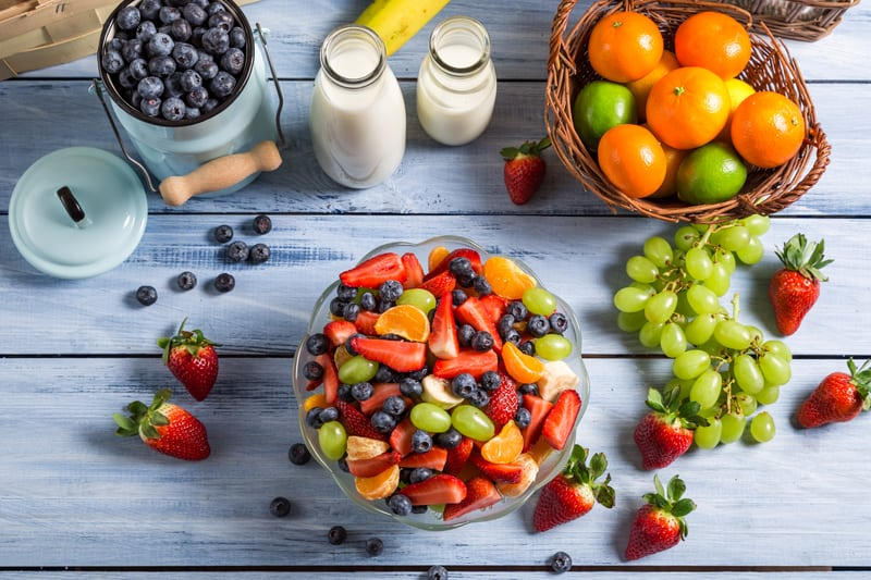 easy fruit salad with berries, oranges, grapes in a bowl against a wood background