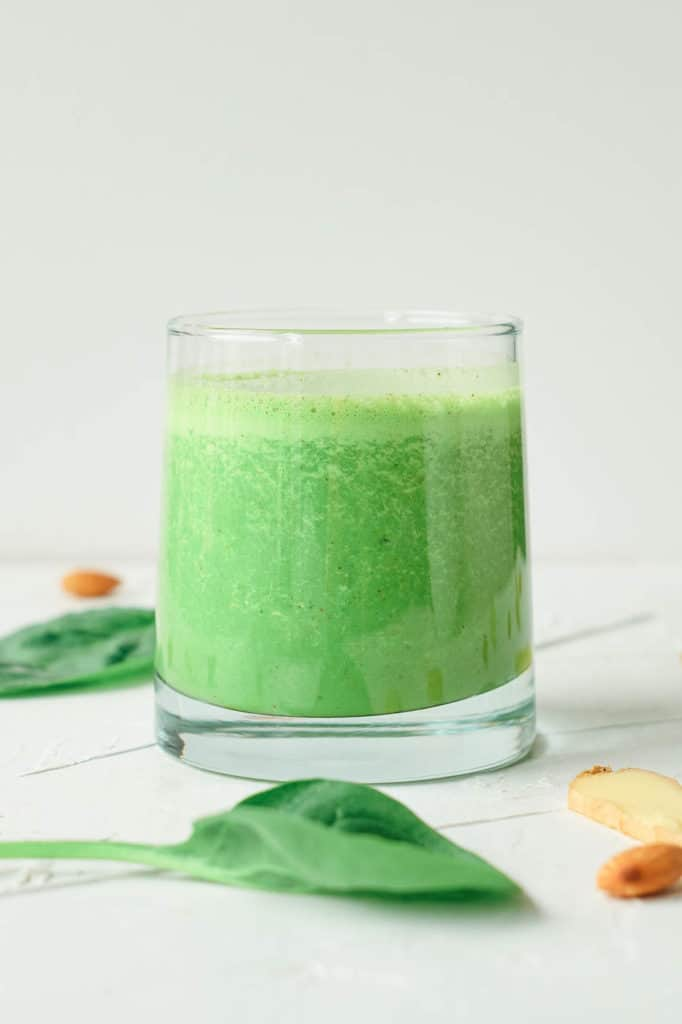 spinach ginger smoothie served in a glass against a white background