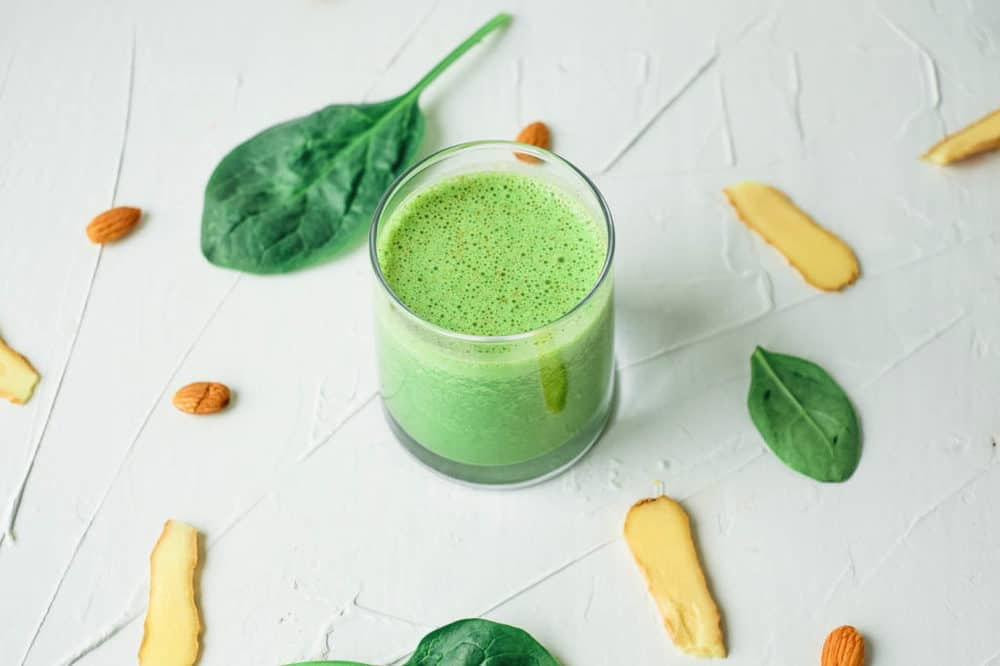 top view of spinach ginger smoothie served in a glass against a white background