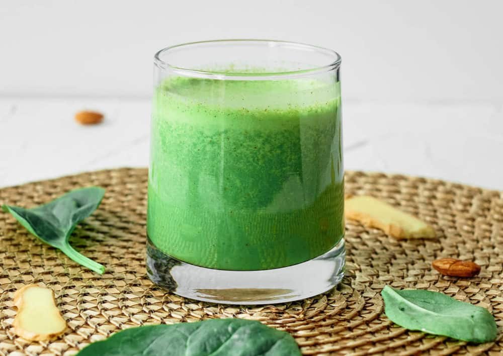 spinach ginger smoothie served in a glass against a brown background