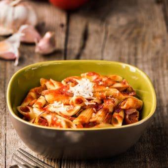 yellow bowl of lentil pasta with marinara sauce