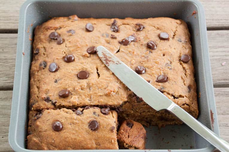 healthy chocolate chip banana bread in a baking tray with a piece cut out