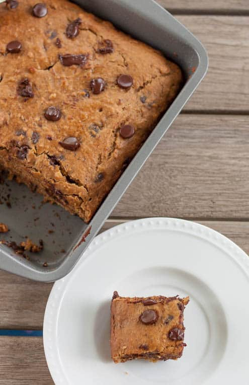 healthy chocolate chip banana bread in a baking tin with a square on a white plate