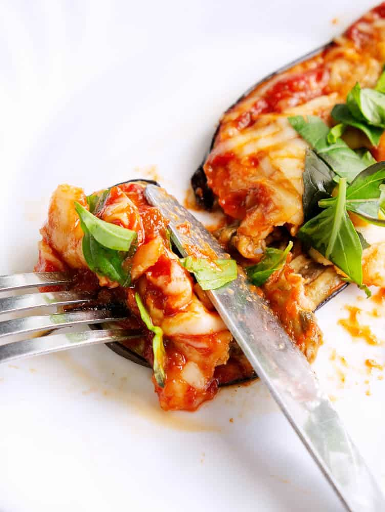 closeup bite of healthy eggplant parmesan with knife and fork