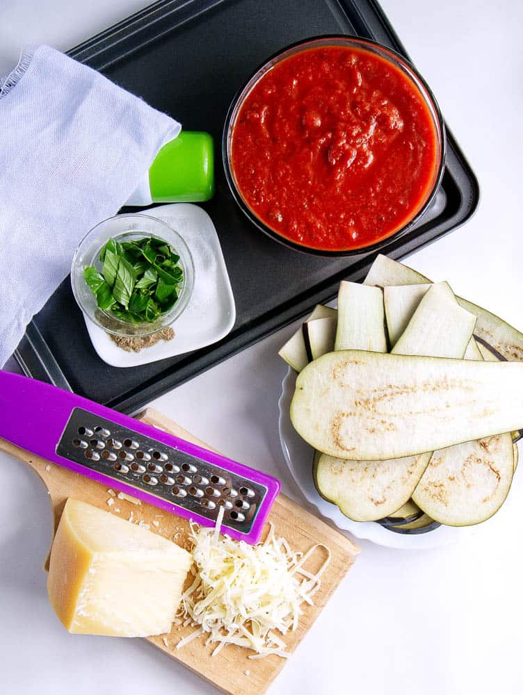 ingredients for healthy eggplant parmesan: marinara sauce, basil, cheese, eggplant slices