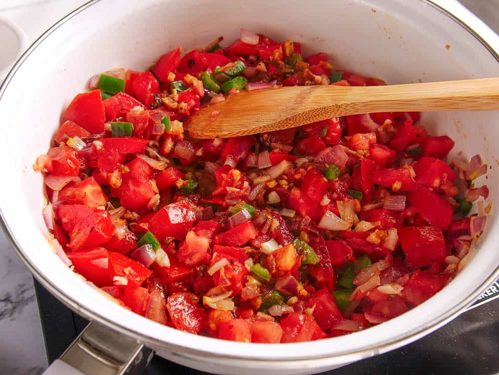 Chopped ingredients (tomatoes, onions, bell peppers, spices) in a pan being stirred