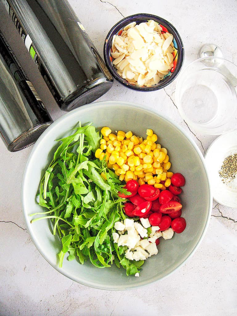 ingredients for spinach and arugula salad with Tomatoes and Goat Cheese: corn, cherry tomatoes, goat cheese, slivered almonds, olive oil, balsamic vinegar, salt, pepper - top view