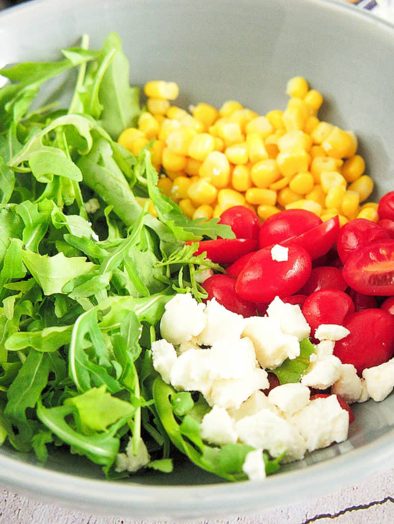 ingredients for arugula corn salad: corn, cherry tomatoes, goat cheese