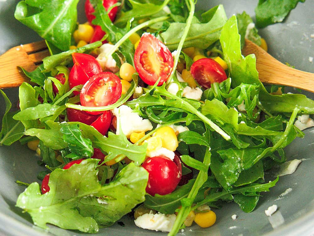 Tossed mixed green salad, with cherry tomatoes and cheese.