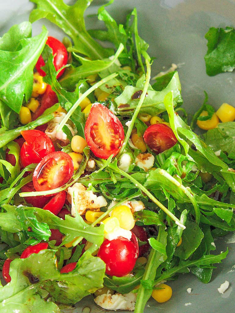 close up of spinach and arugula salad with cherry tomatoes and goat cheese, served in a light blue salad bowl