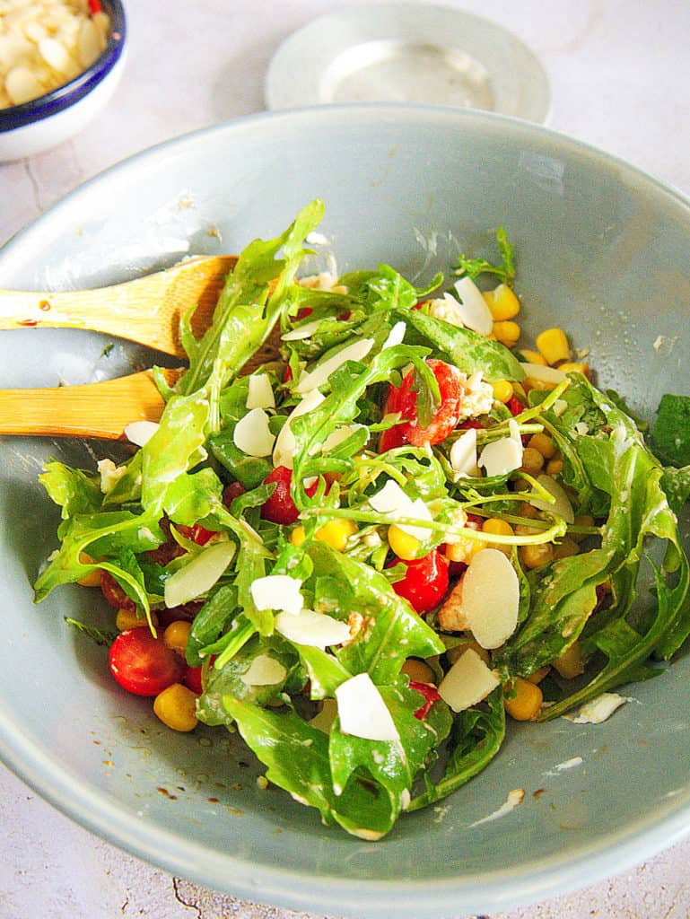 spinach and arugula salad with Tomatoes and Goat Cheese served in a light blue salad bowl