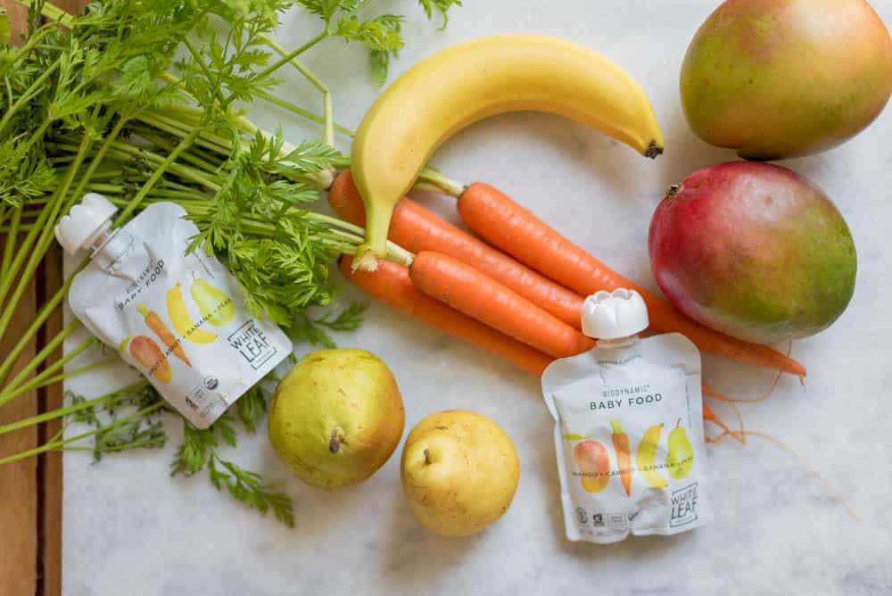 white leaf provisions baby food pouches on a white backdrop, surrounded by fresh mangoes, bananas, pears, carrots