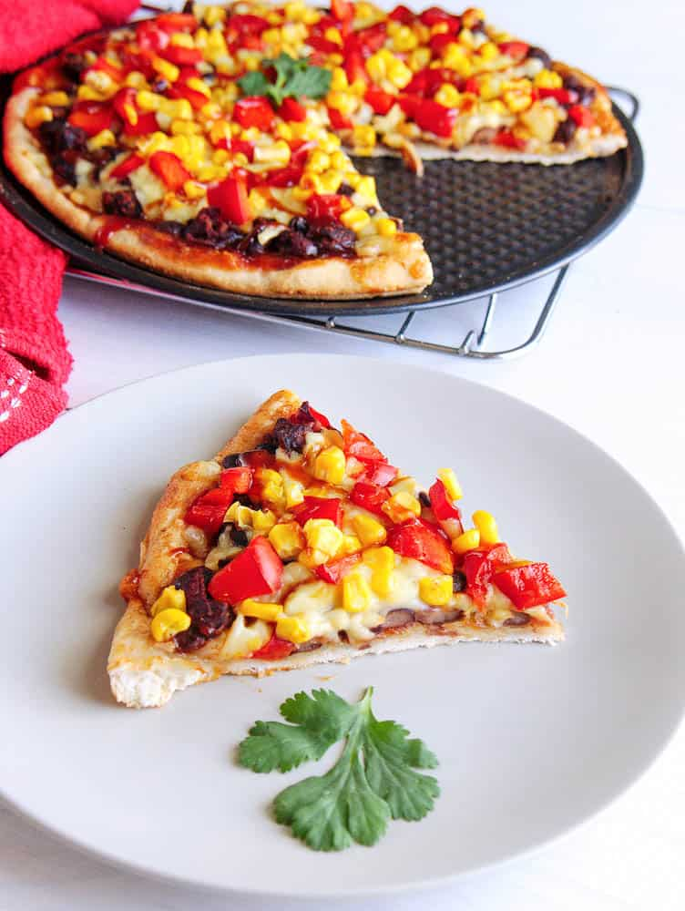 A slice of black bean and corn pizza on a white plate