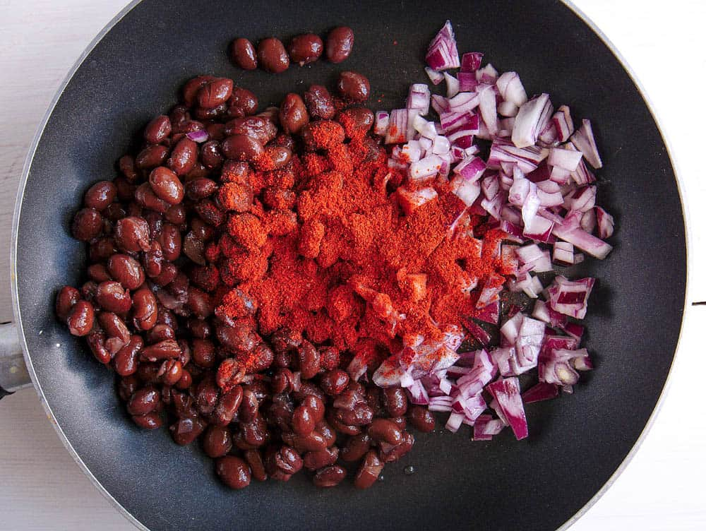 Onions, chili and beans in a frying pan