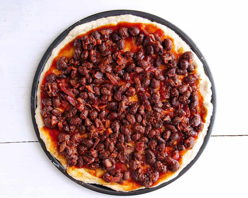 The cooked black beans spread on the pizza dough