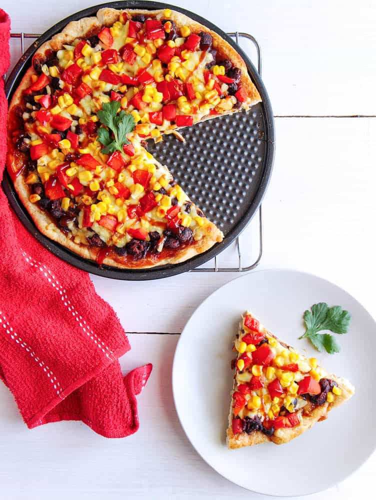 A barbecue, black bean and corn pizza on a baking sheet with a slice on a white plate