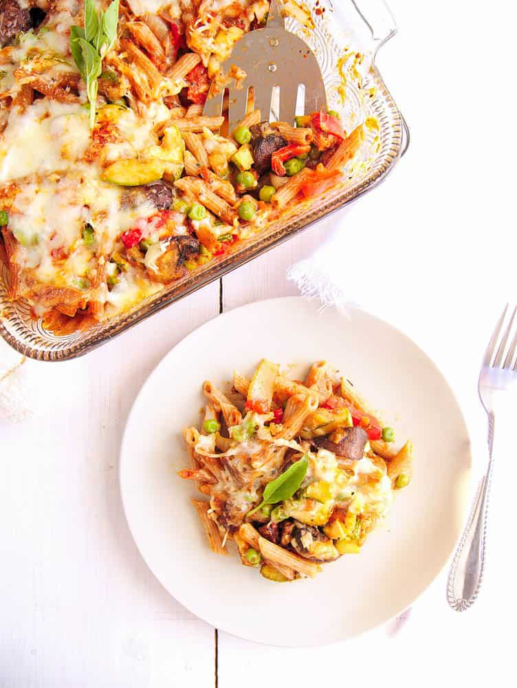Baked penne pasta with roasted vegetables served on a white plate