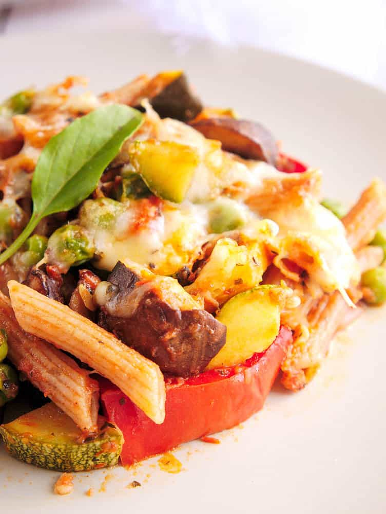Close up of baked penne pasta with roasted vegetables on a white plate
